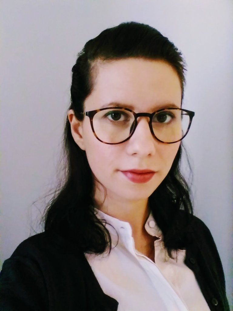Portrait of Christina Ditinca against grey background.