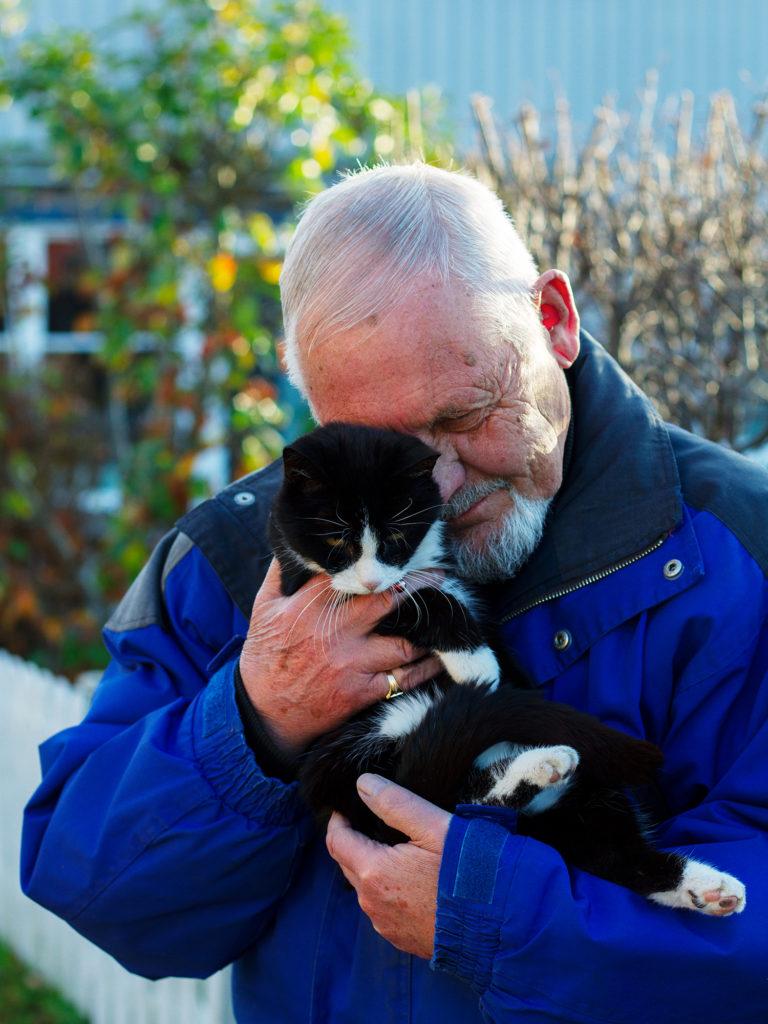 Older man hugging cat, outside