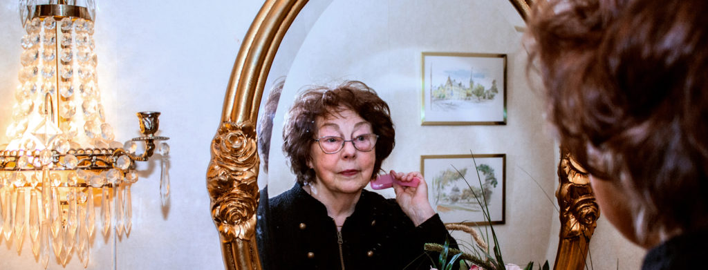Vivi-Anne Hallin Karlsson fixing her hair in front of a mirror.