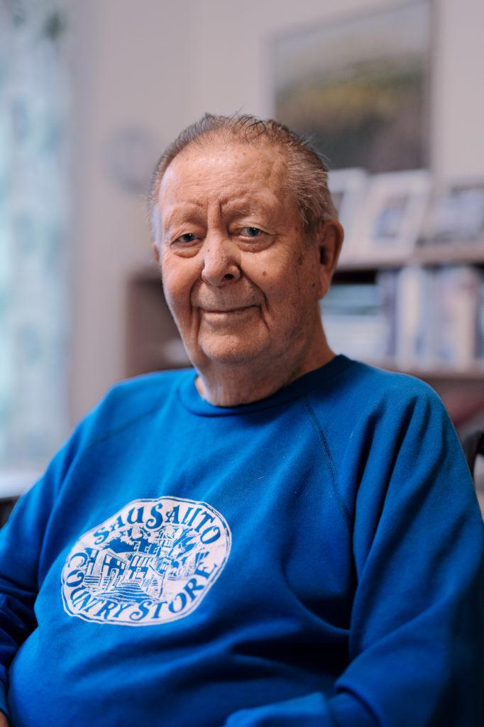 Portrait of Jonas Enarsson in blue sweater sitting in chair.