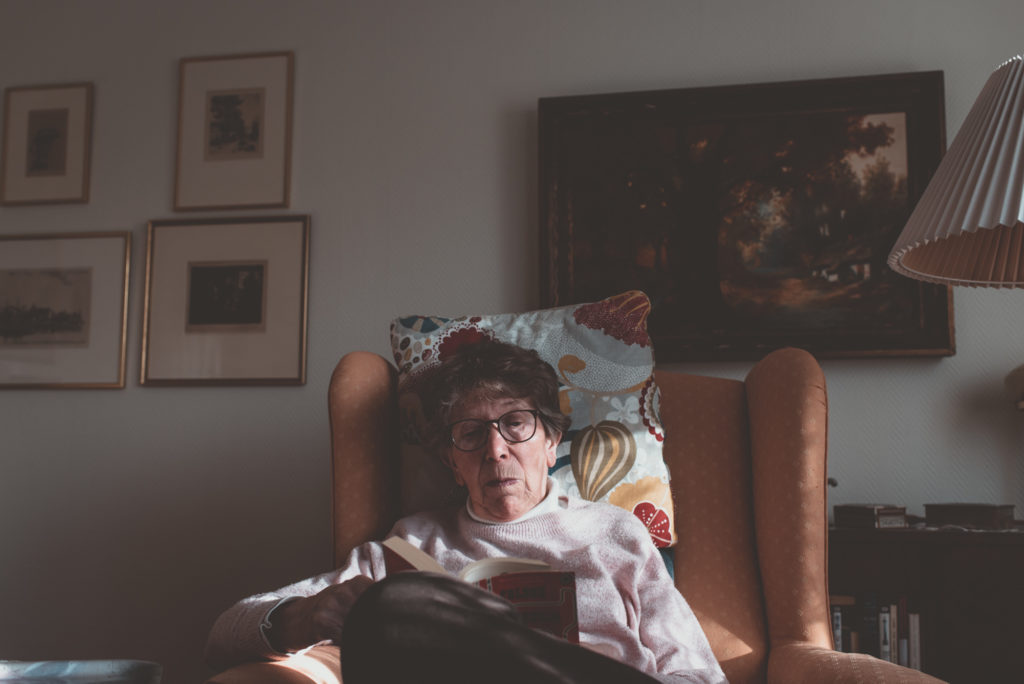 Britta Zarmén in armchair, reading a book