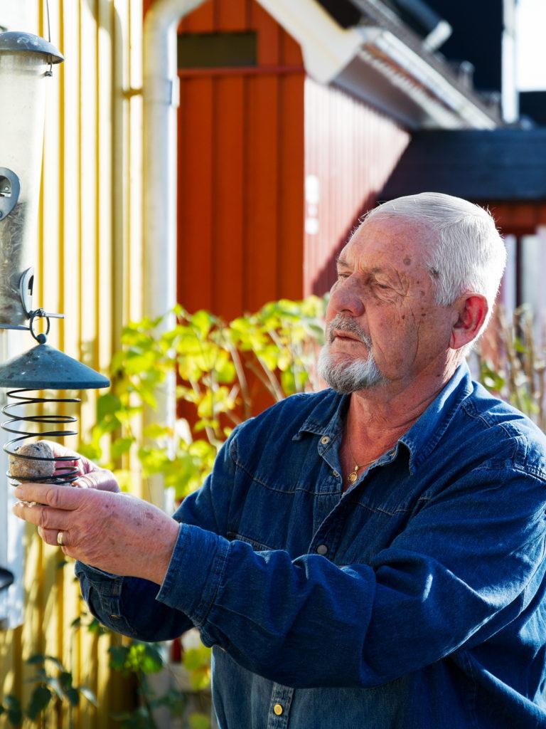 Bengt Malmström outside, filling up birdfeeder