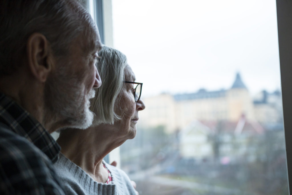 Older couple looking out their window, man standing closer to the camera slightly behind his wife.